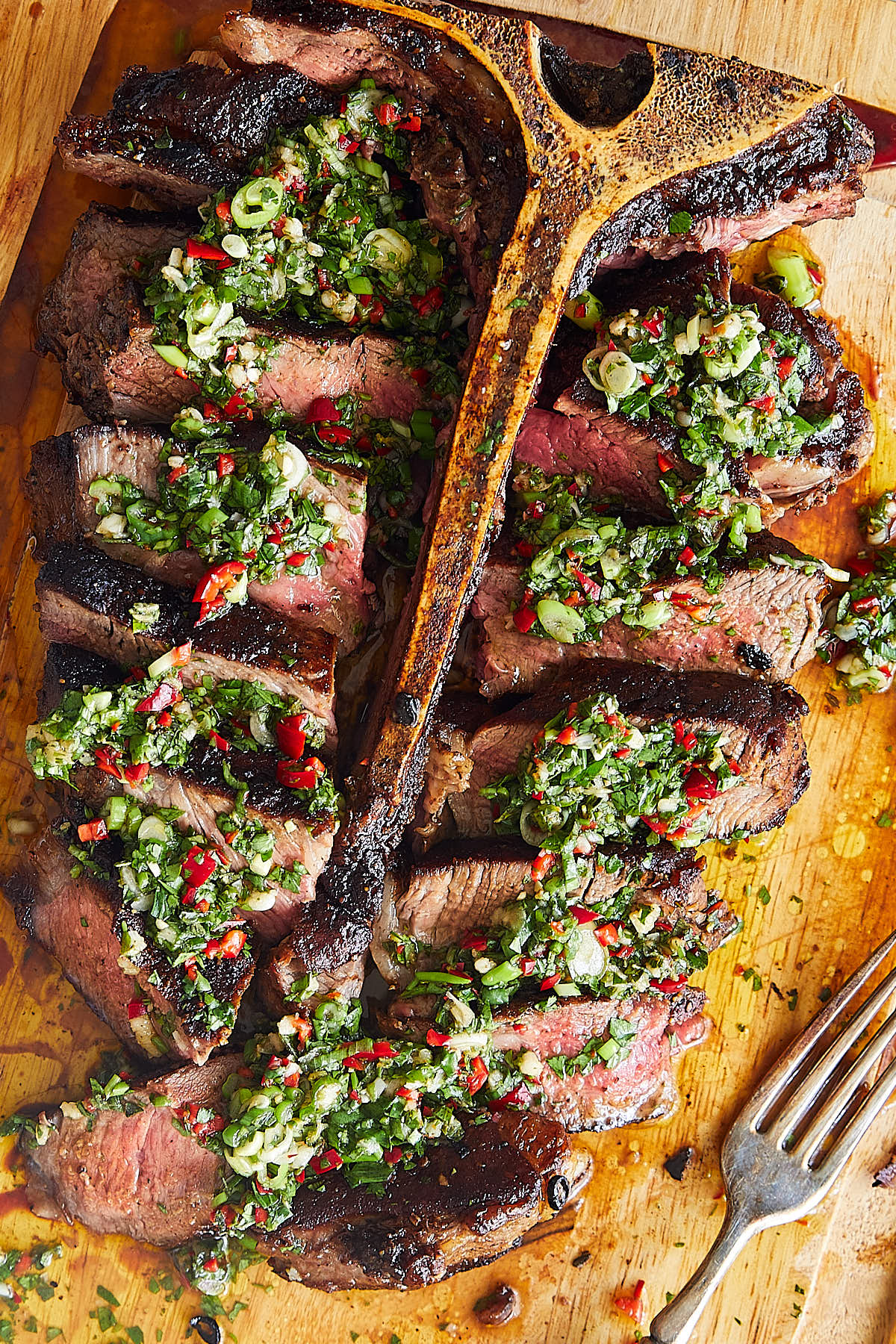 Sliced Porterhouse Steak with chimichurri on top.