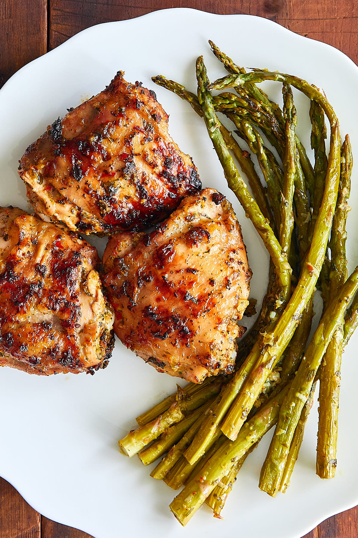 Grilled chicken thighs on a plate with asparagus.