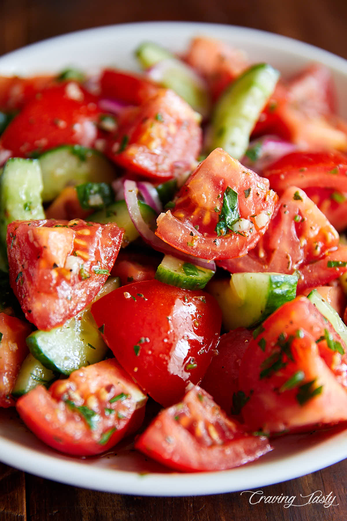 Close up of juicy, chunky tomatoes and cucumbers covered in dressing.