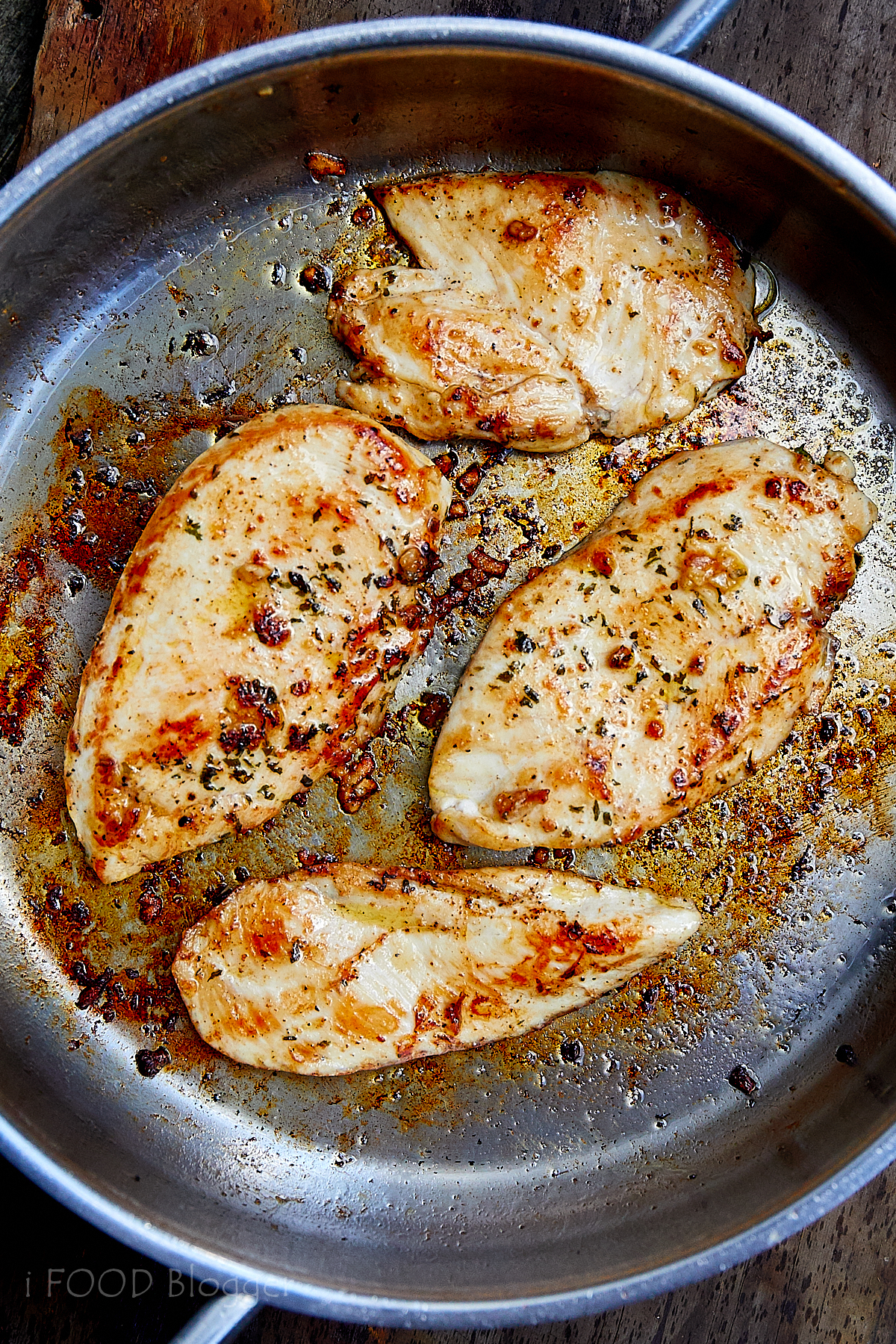 Four golden brown pan-fried chicken breasts in a stainless steel pan.