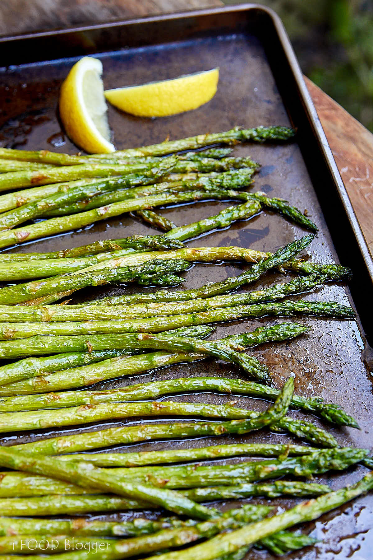 Broiled asparagus with lemon on a baking sheet.