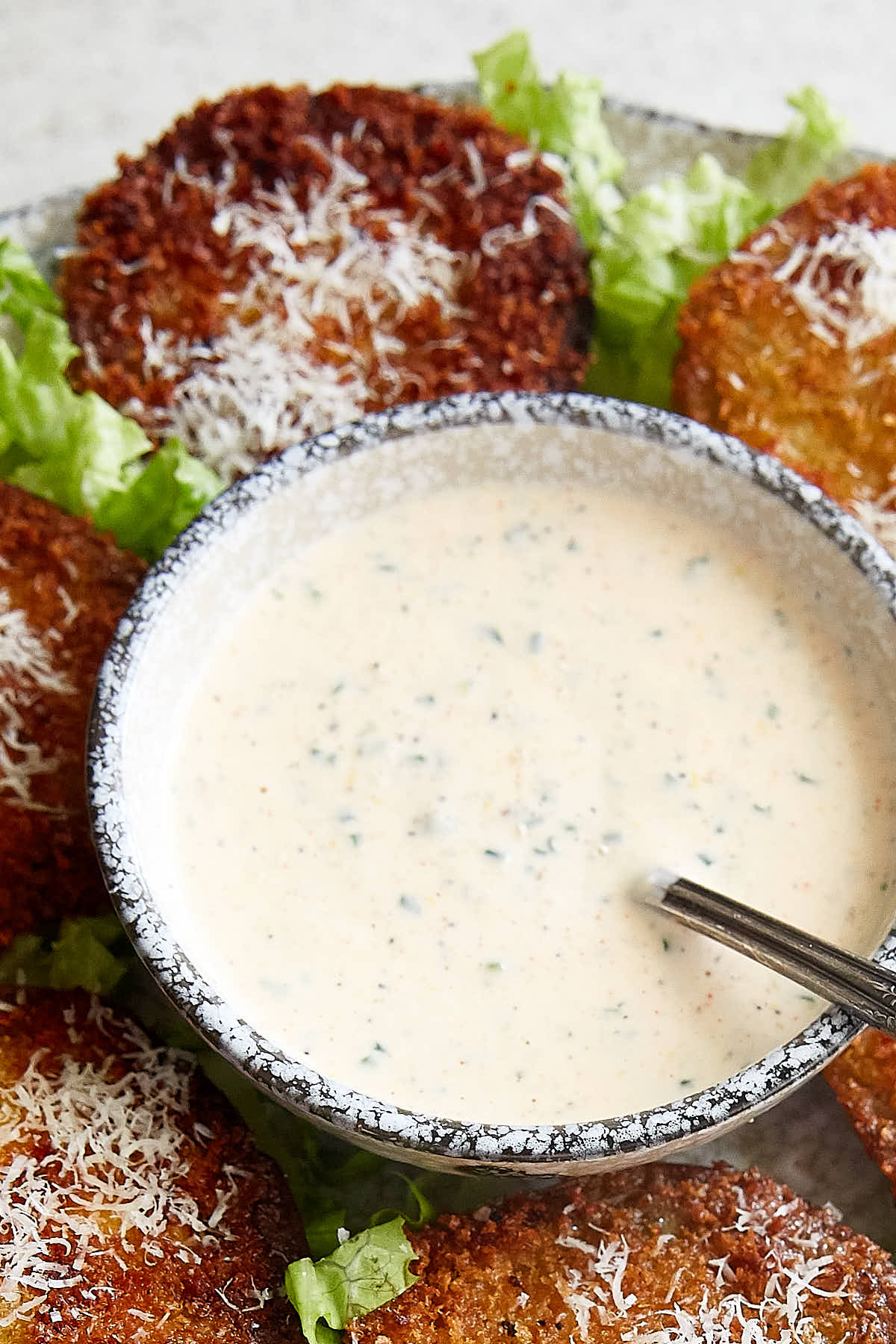 A grey speckled bowl filled with homemade buttermilk ranch dressing, with a spoon inside and fried tomatoes arranged around it.