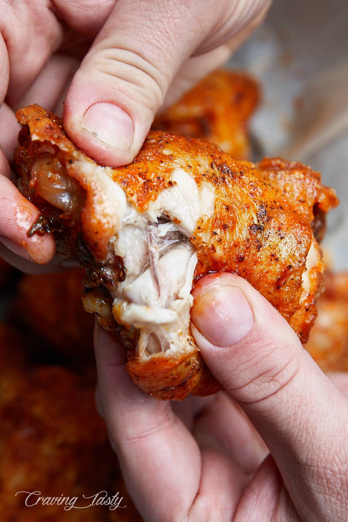 Close up of a split open crispy chicken thigh, showing juices running off.