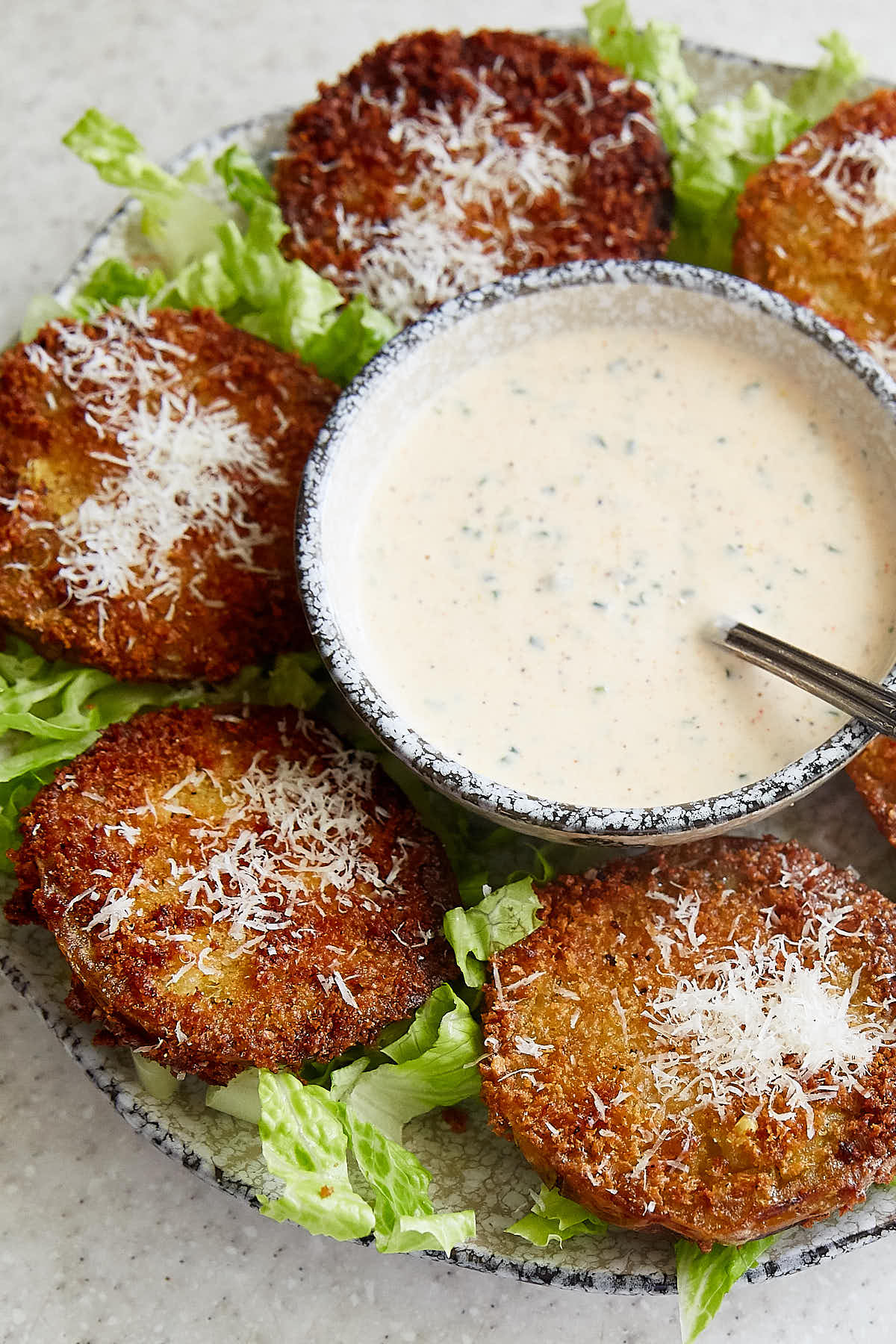 A bowl of ranch dressing next to fried green tomatoes.