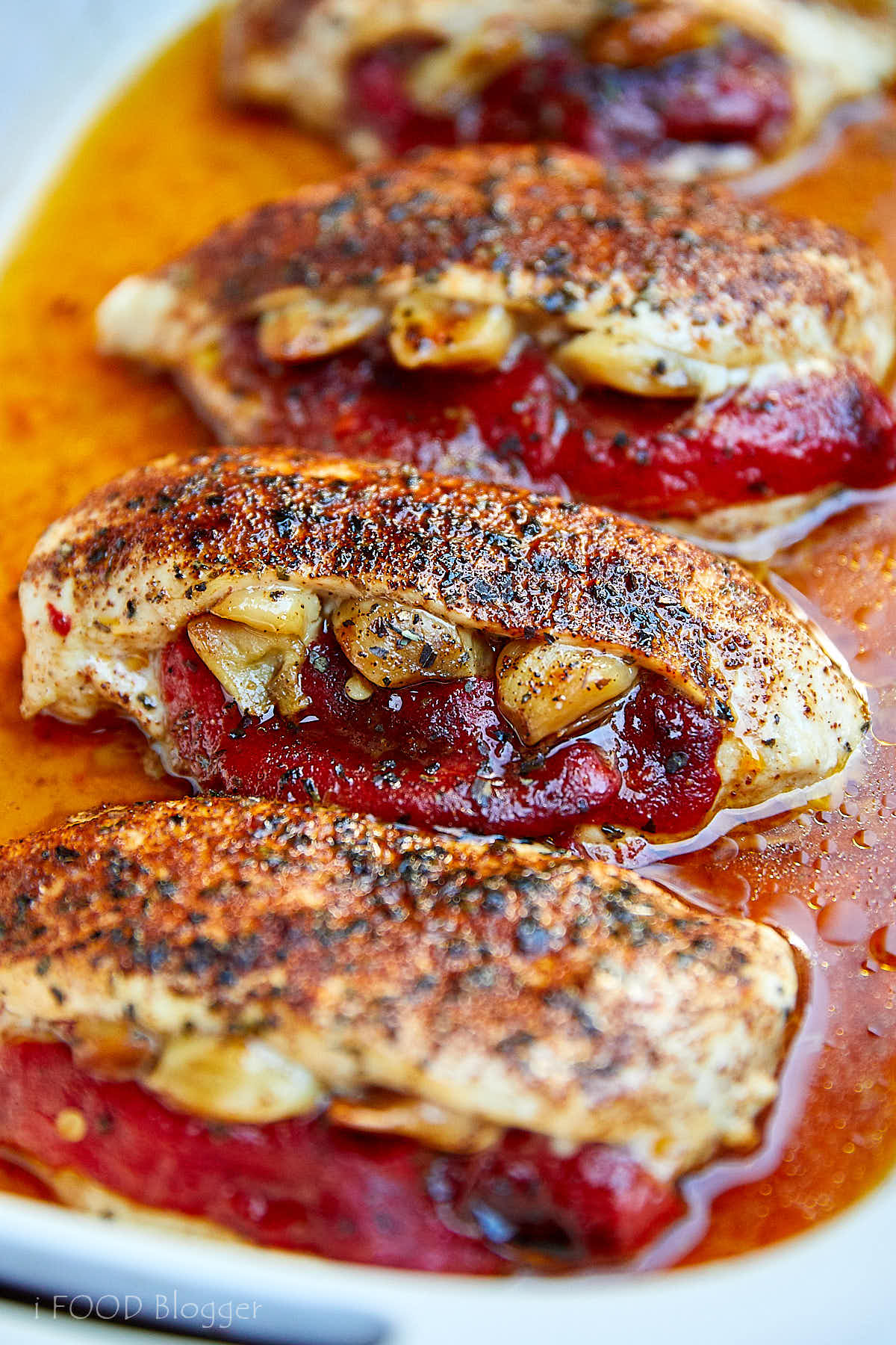 Stuffed baked chicken breasts in baking dish with pan juices on the bottom.