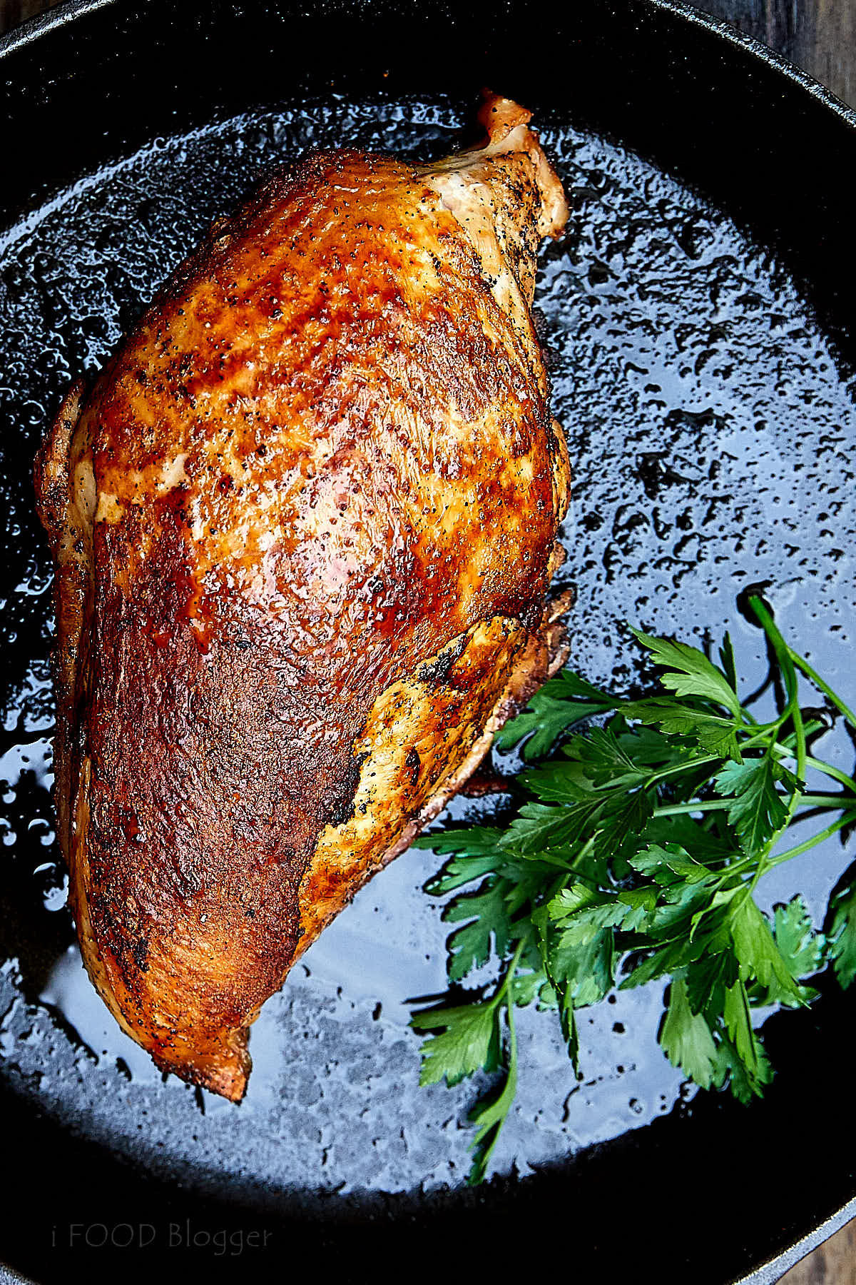 Close up of a golden-brown, crispy bone in turkey breast on a cast iron pan.