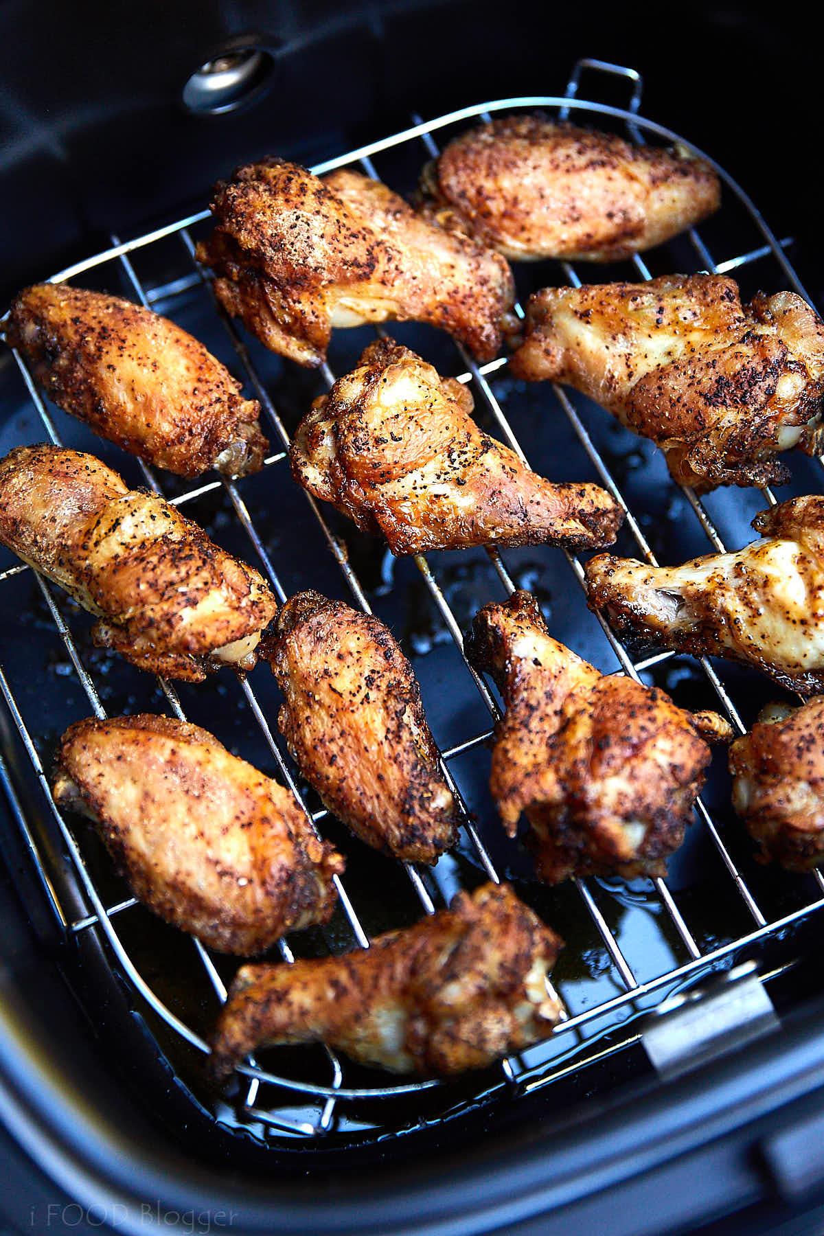 Golden-brown chicken wings on a rack of an air fryer.