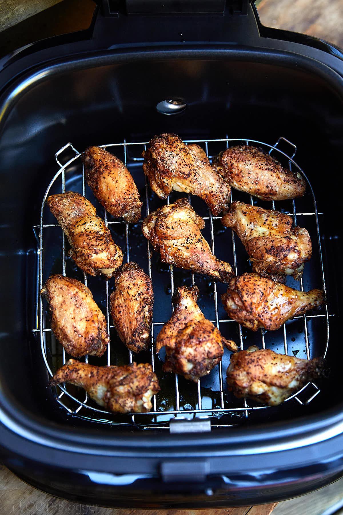 Crispy browned chicken wings inside an open air fryer.
