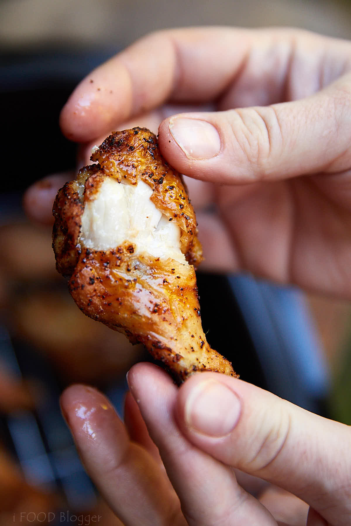 Close up of an air fried chicken wing, split open, showing juicy and moist meat under crispy skin.