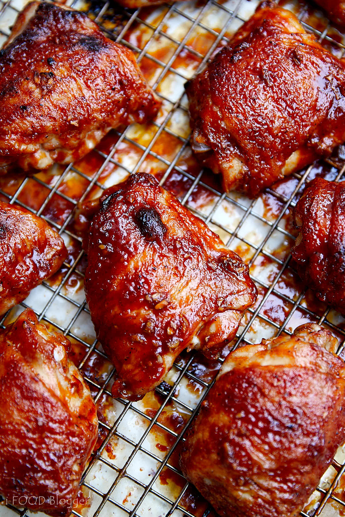 Well-browned chicken thighs glazed with BBQ sauce on a cooling rack over a baking sheet.
