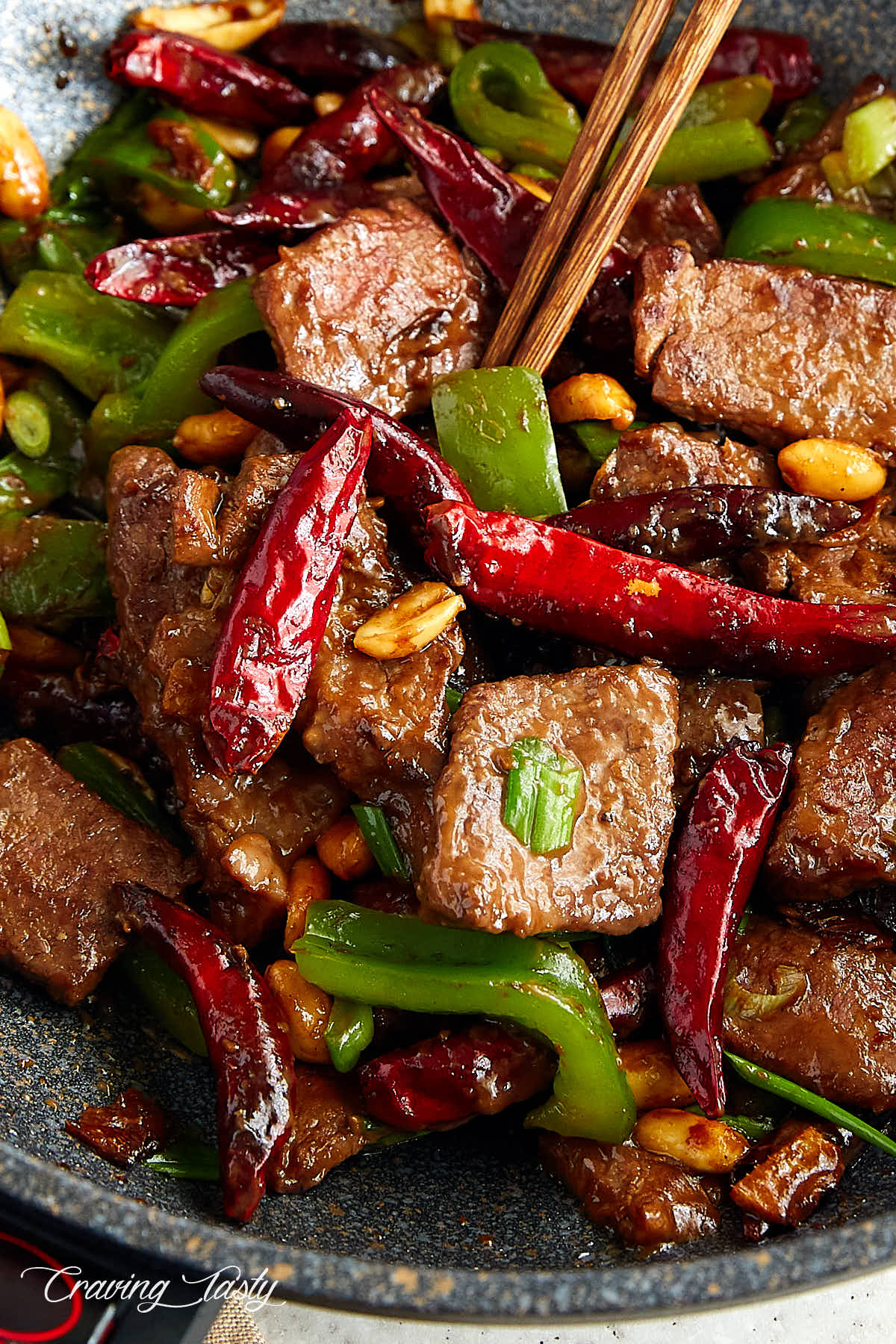 Kung pao style beef, in a wok with hot peppers, peanuts, and bell peppers.