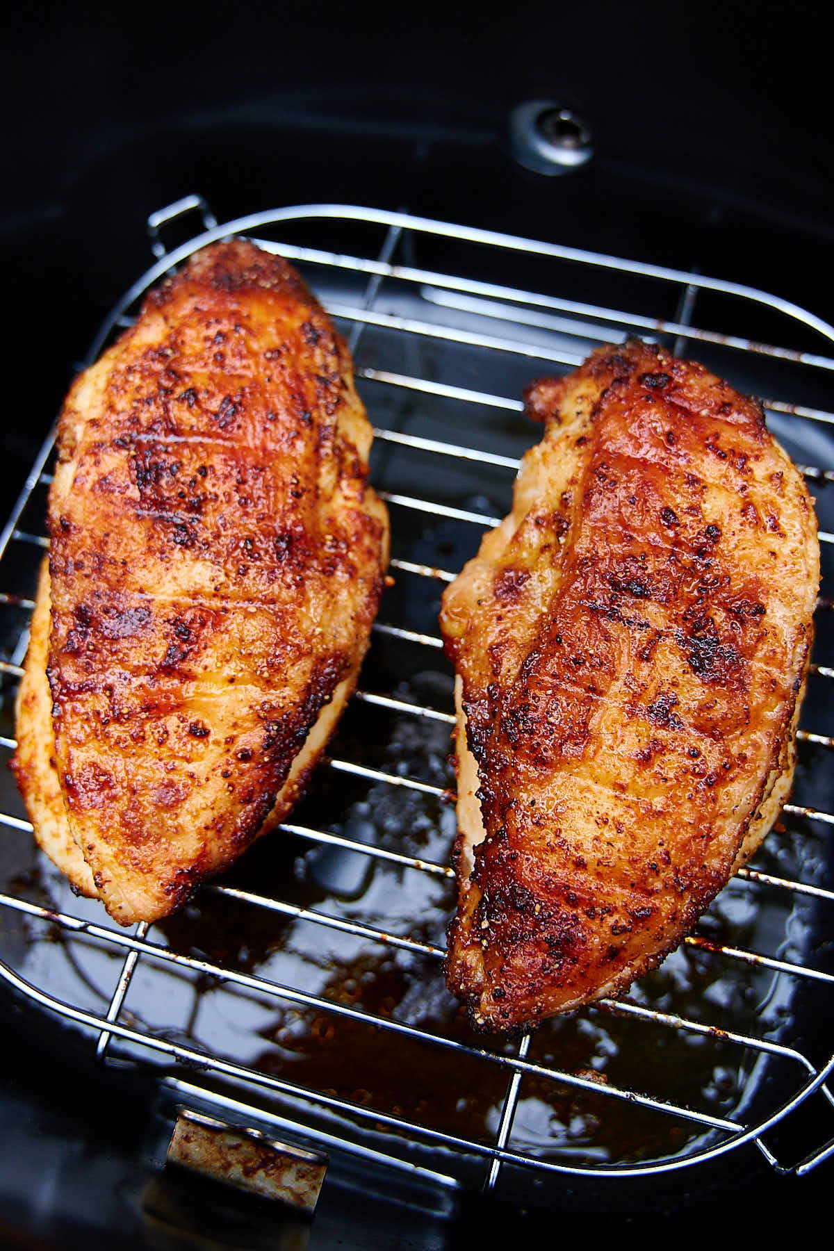 Two crispy, golden brown air fried chicken breasts sitting on a rack inside an air fryer.