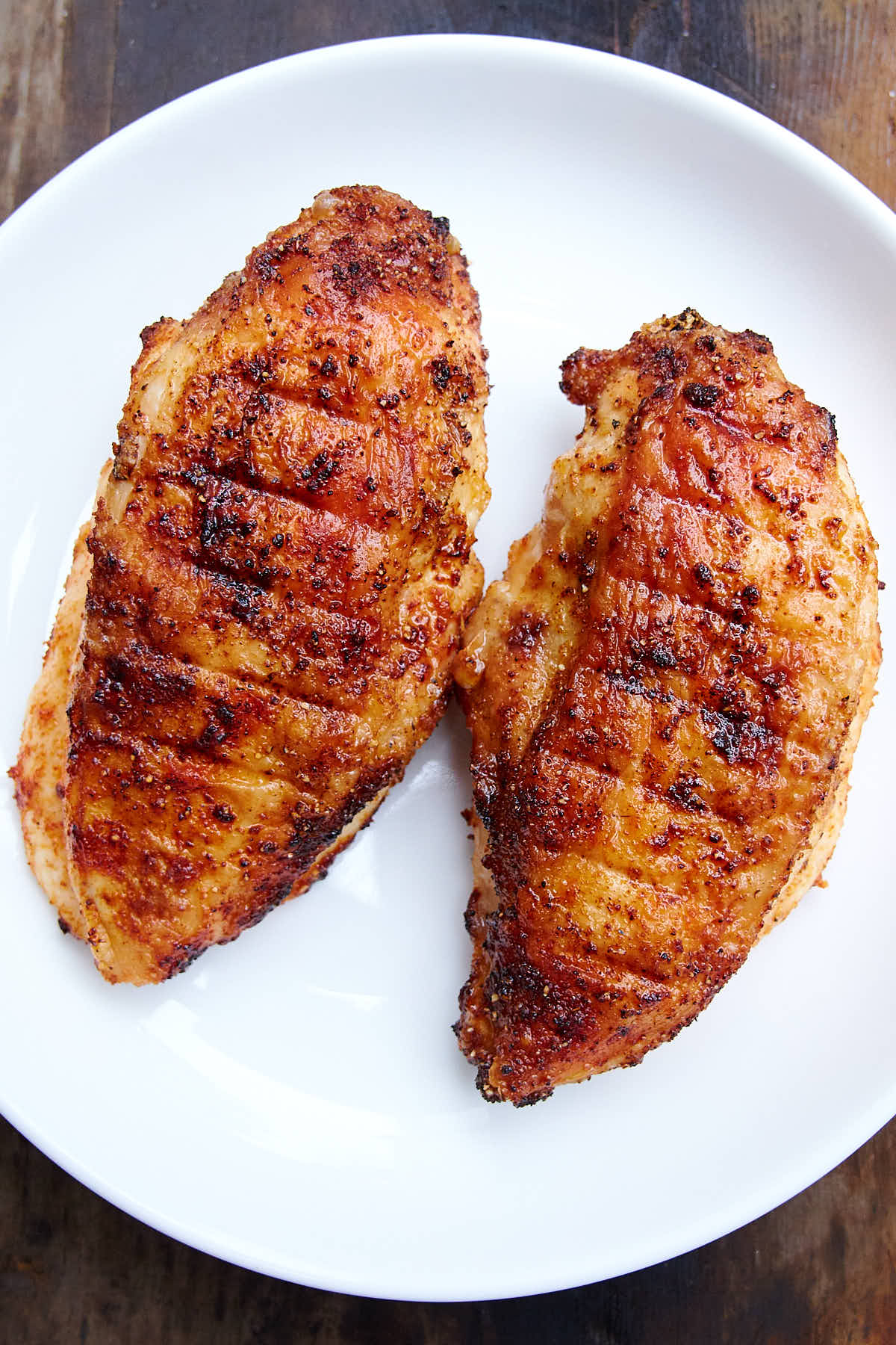 Deep golden-brown, crispy air fried chicken breasts on a white plate.