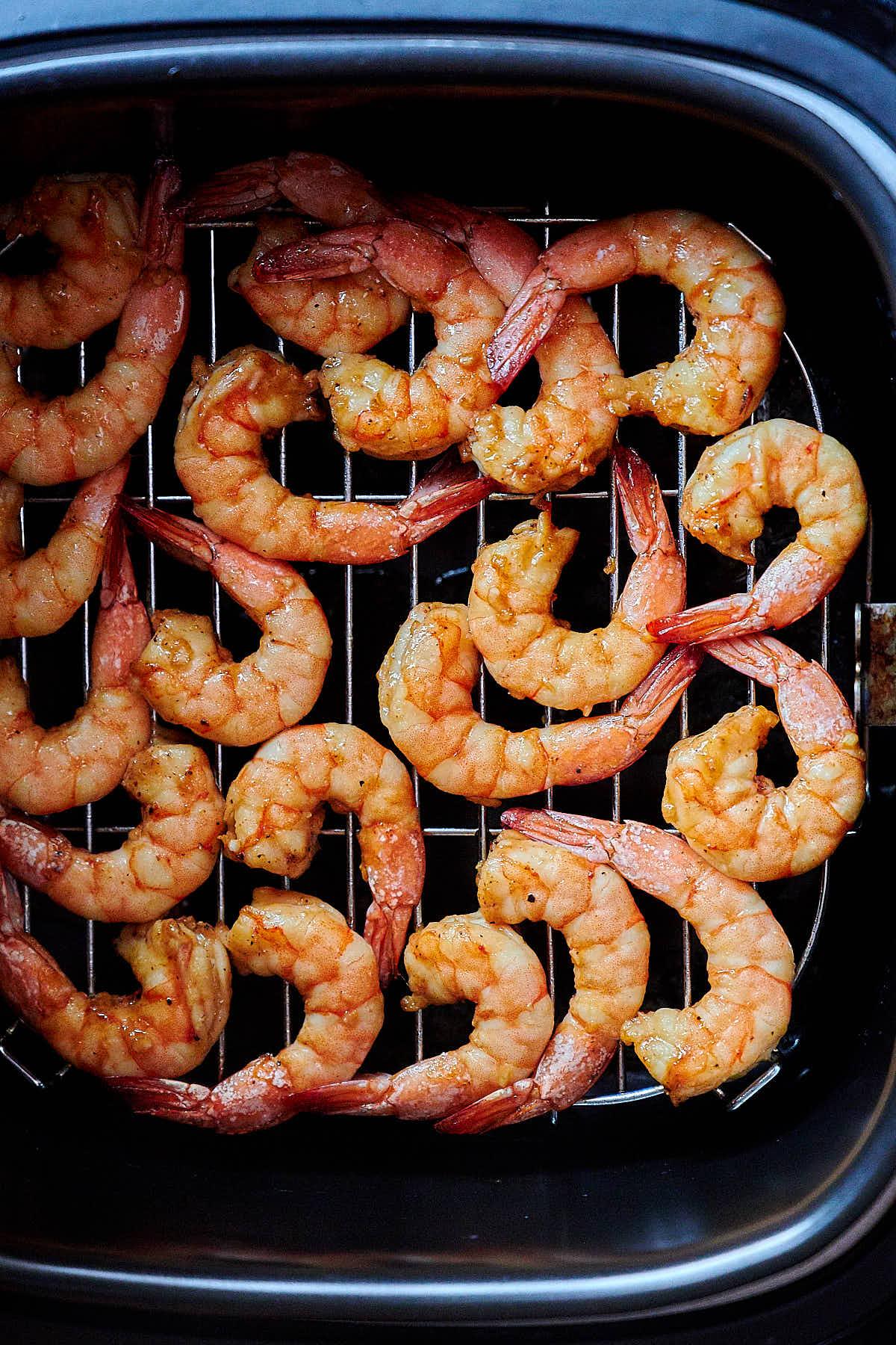 Shrimp cooking inside an air fryer.