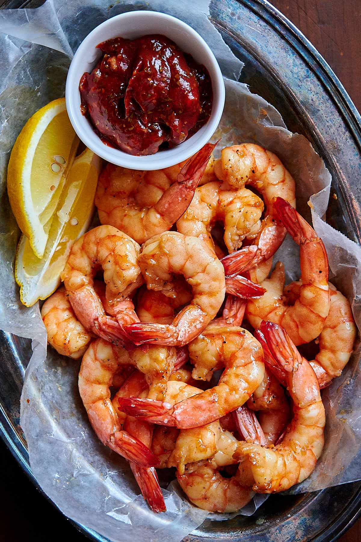 Air fried shrimp in a basket lined with white wax paper, with a lemon wedge a saucer with sauce on the side.