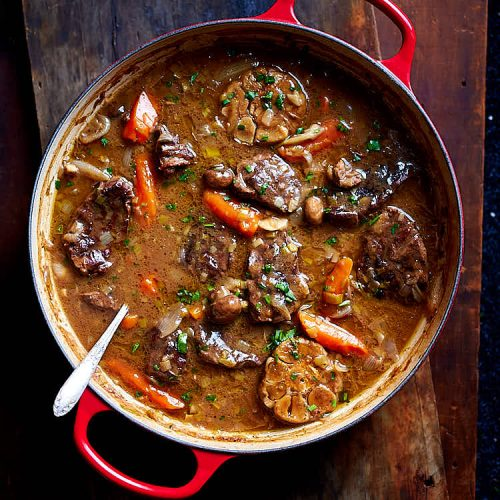 Braised beef cooked in a cast iron braising pan with mushrooms, leeks, carrots, onions, shallots and garlic. The sauce is thick and velvety smooth, like gravy. No thickening is needed after braising. Simply remove from the oven and serve with a side dish of choice. | ifoodblogger.com