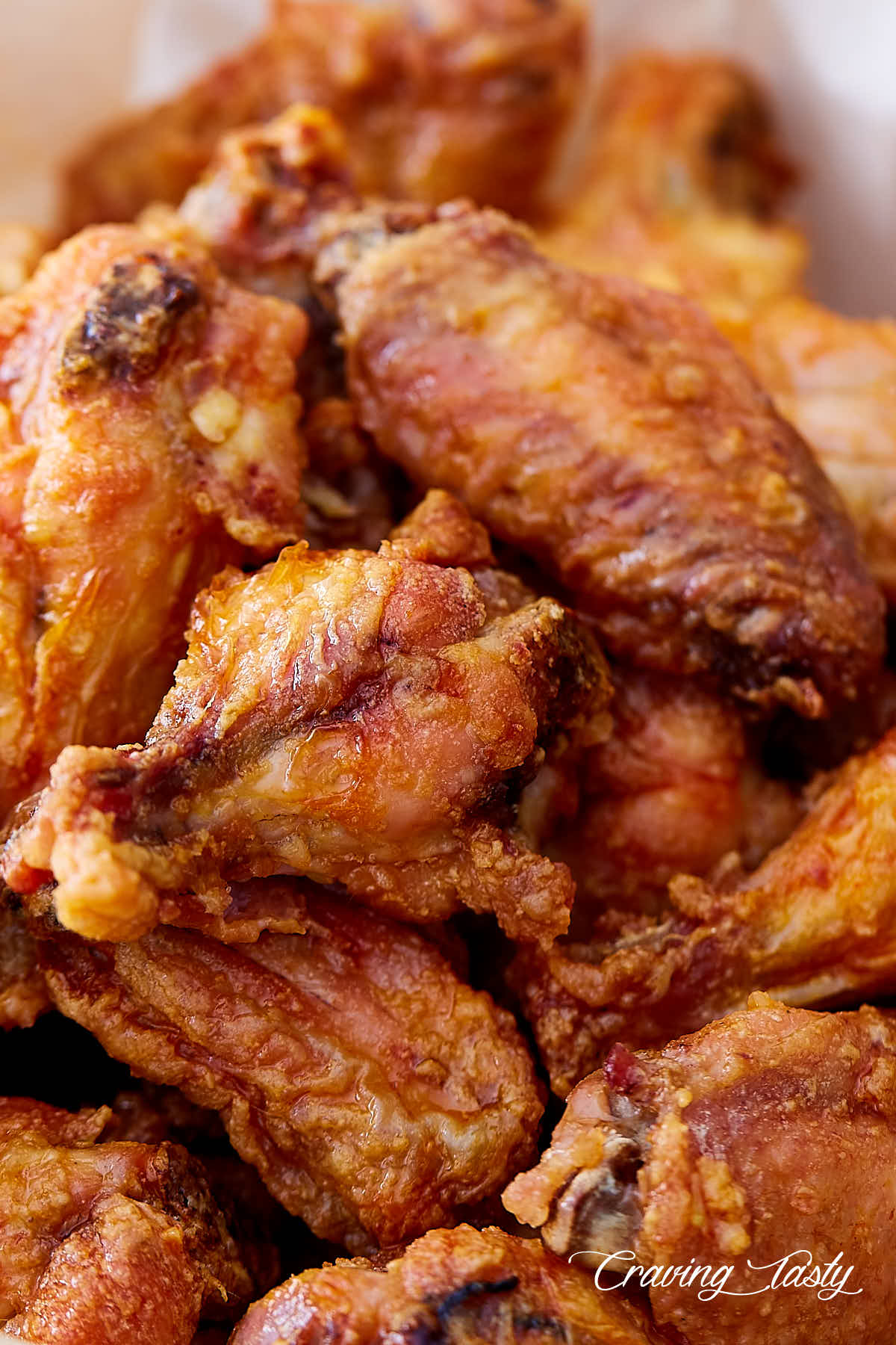 Close up of extra crispy chicken wings in a serving basket.