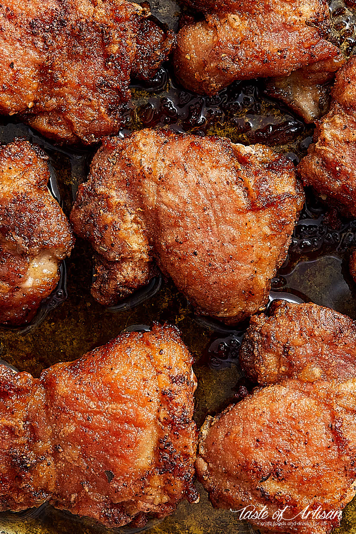 Close up of super crispu pan-fried boneless skinless chicken thighs on a skillet.
