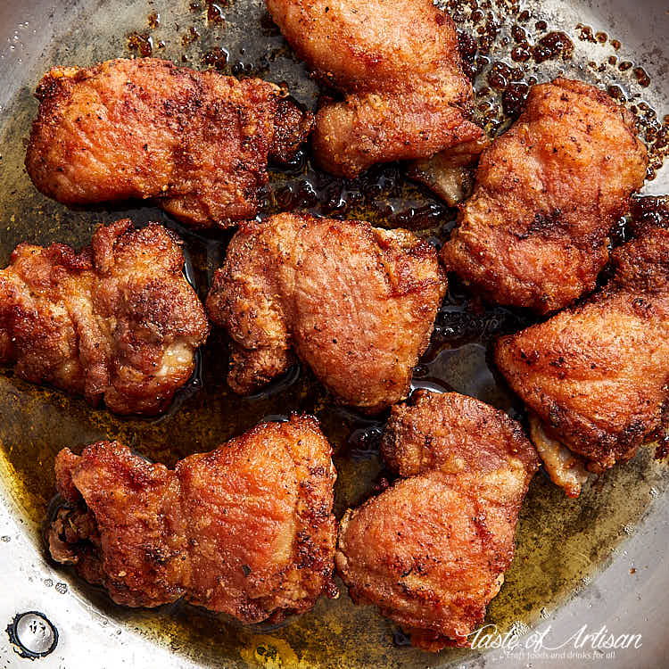 Topo down view of golden brown, crispy boneless skinlees chicken thigh in a frying pan.