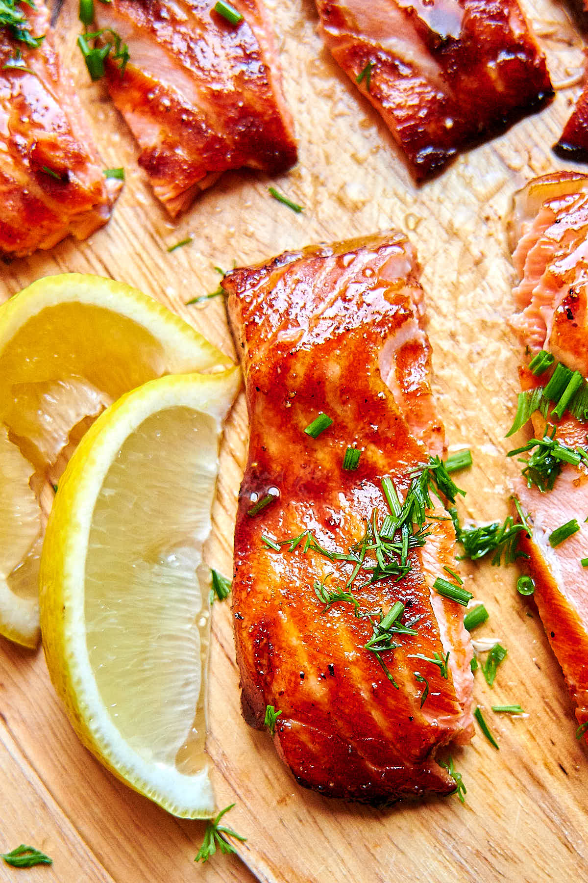 Close up of air fried salmon filet pieces with chopped dill on top, with lemon wedges on the side, on a cutting board.