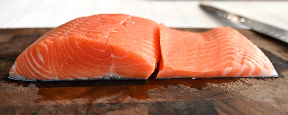 View of salmon filet with thick and thin parts split apart.