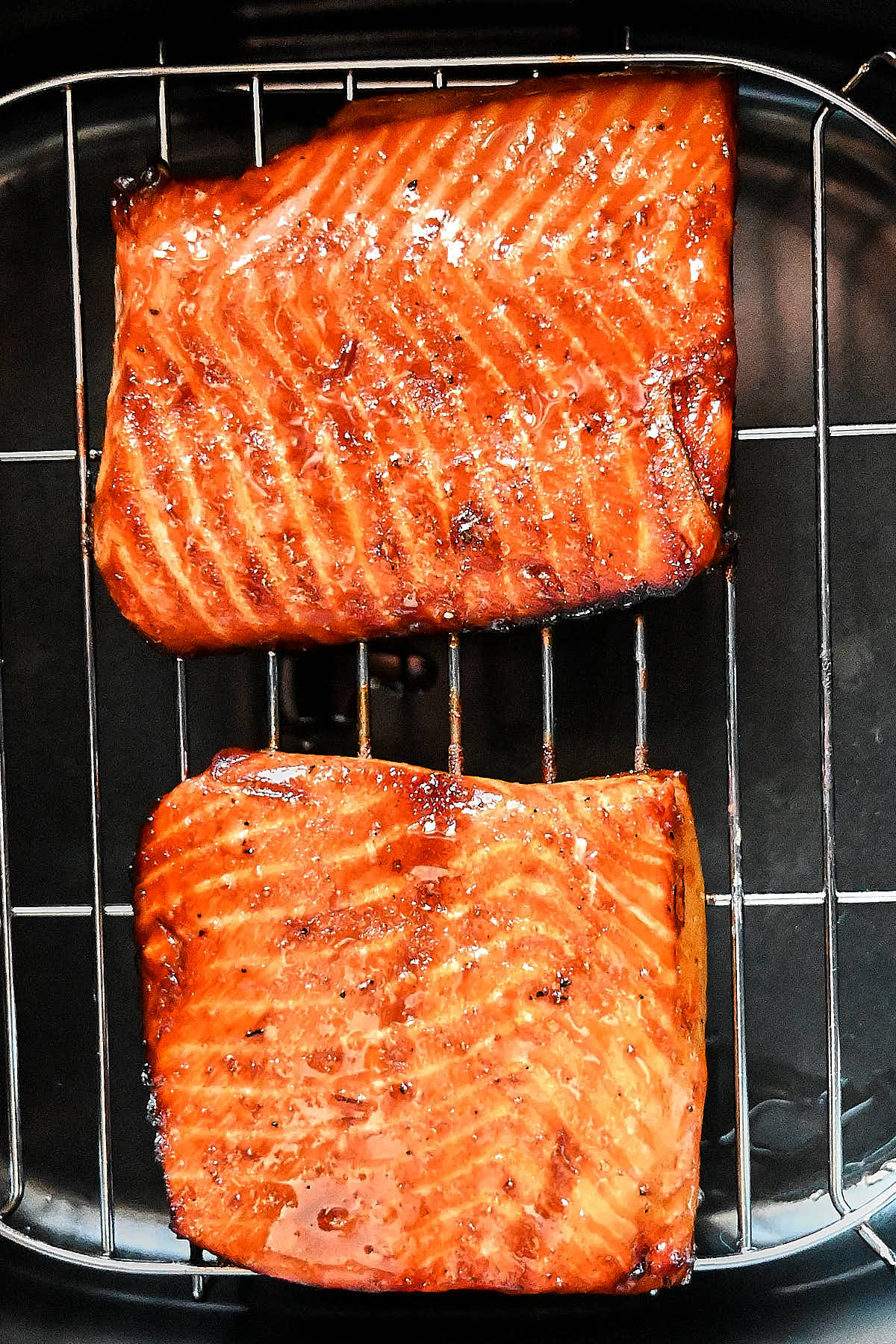 Air fried salmon pieces inside an air fryer on a rack.