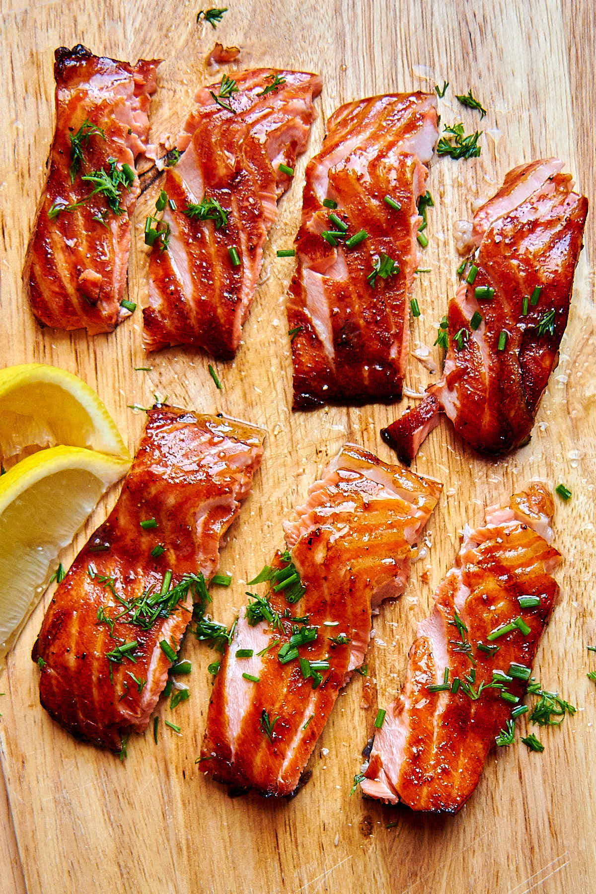 Air fried salmon filet pieces on a cutting board with lemon wedges on the side.