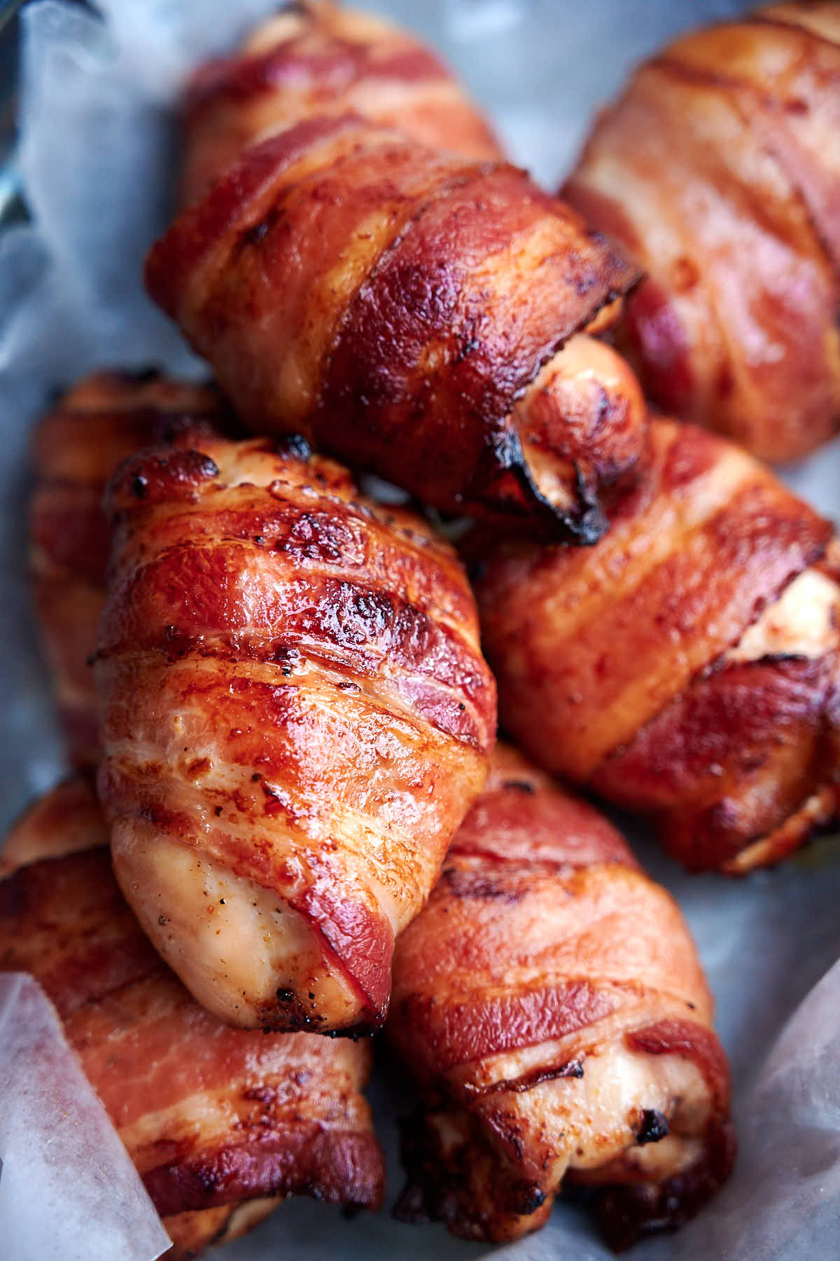 Chicken thighs wrapped in bacon, cooked, in basket lined with white wax paper.