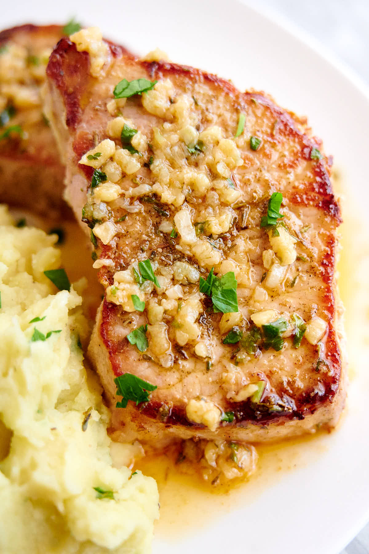 A delicious, juicy baked pork chop on a plate.