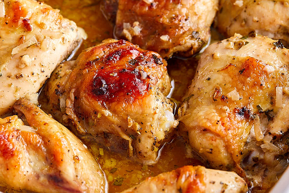 Close up of roasted mojo chicken in a white baking dish.