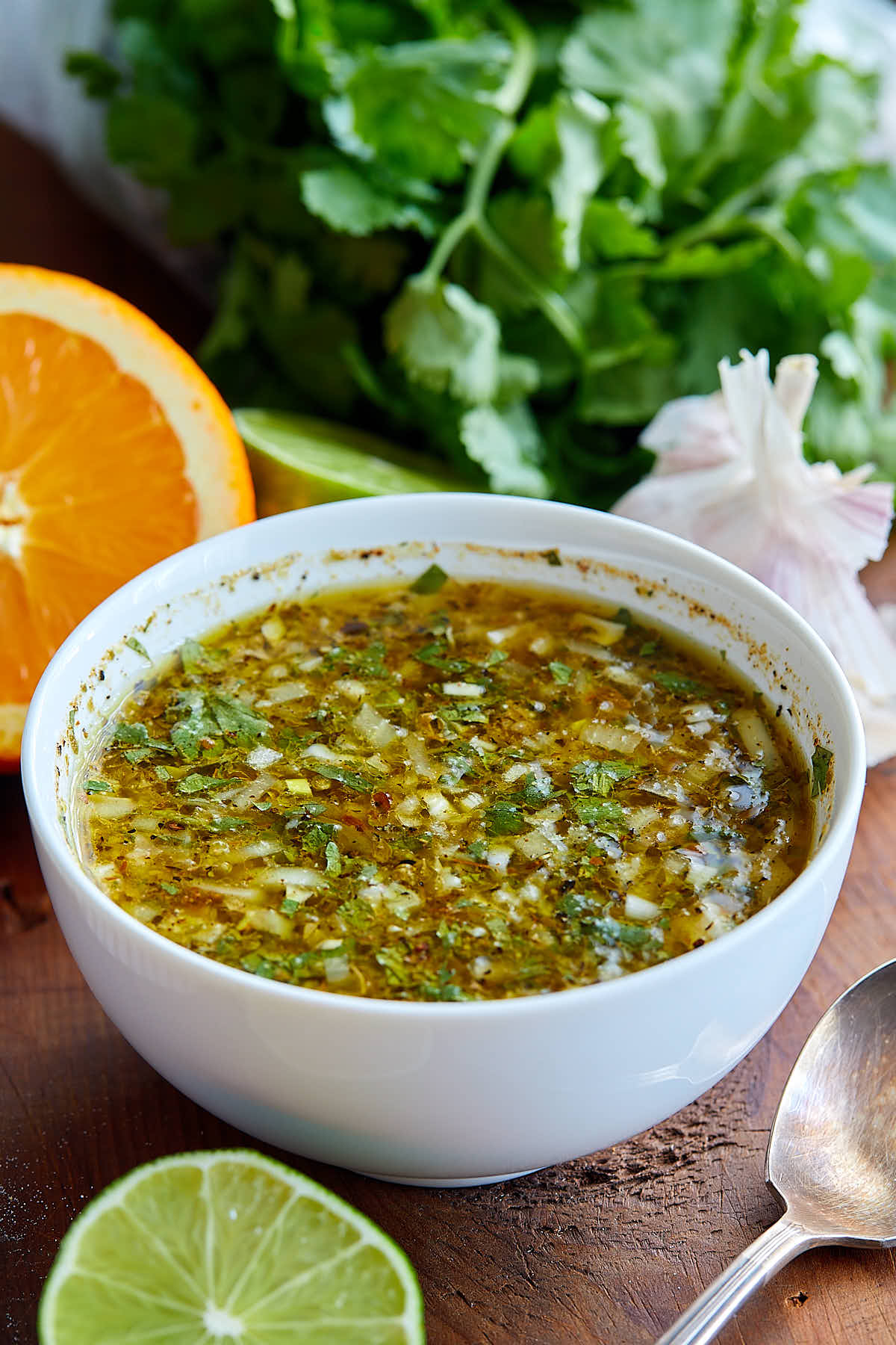 Cuban mojo marinade in a white bowl, surrounded by parsley, garlic, cut lime and orange.