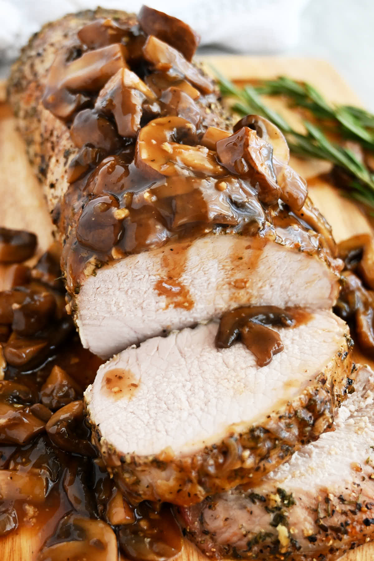 Roasted pork loin, on a cutting board, mushroom sauce on top.