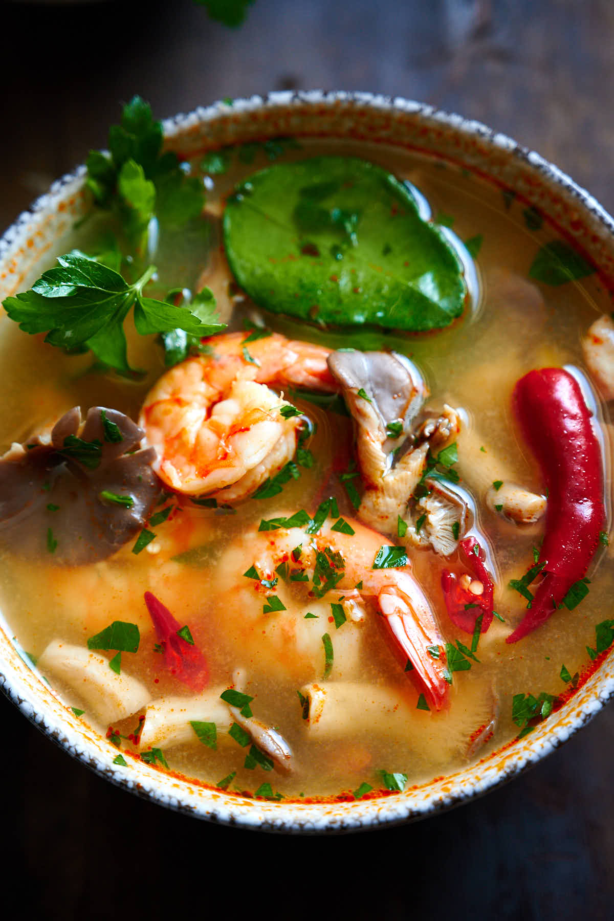 Tom yum soup in a speckled bowl - prawns, mushrooms, lime leaf, cilantro and red chiles in amber soup.