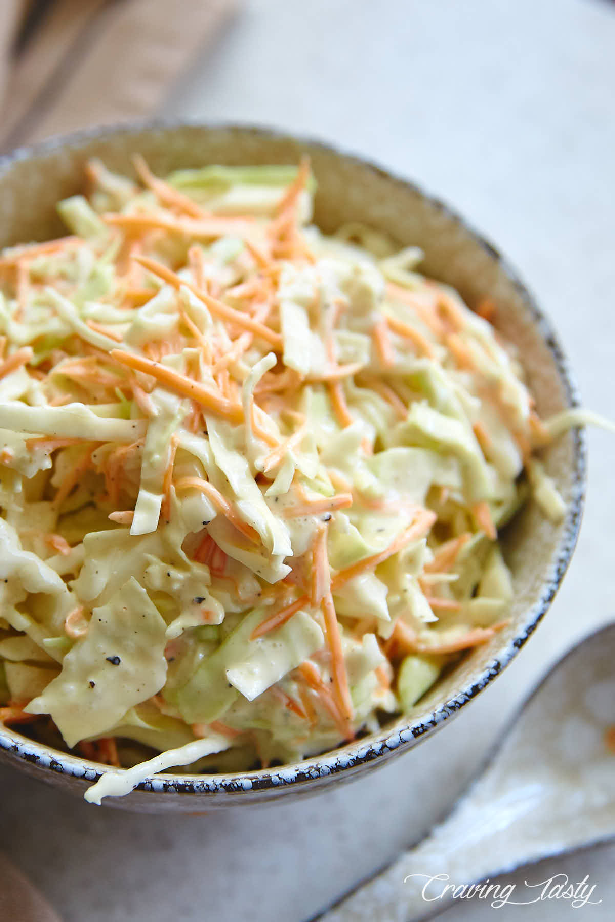 Homemade coleslaw inside a speckled grey bowl, on a table with a spoon next to the bowl.