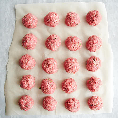 Shaped meatballs on a piece of parchment paper.