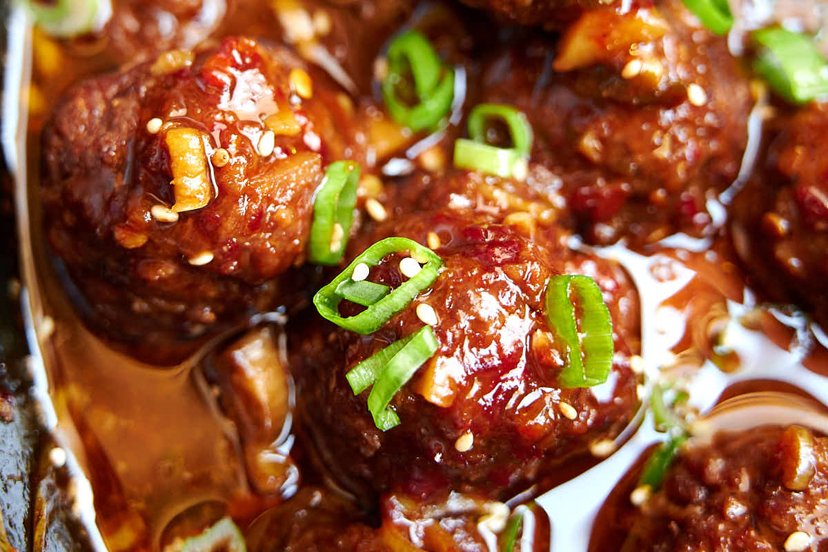 Close up of Asian meatballs covered in red sauce.
