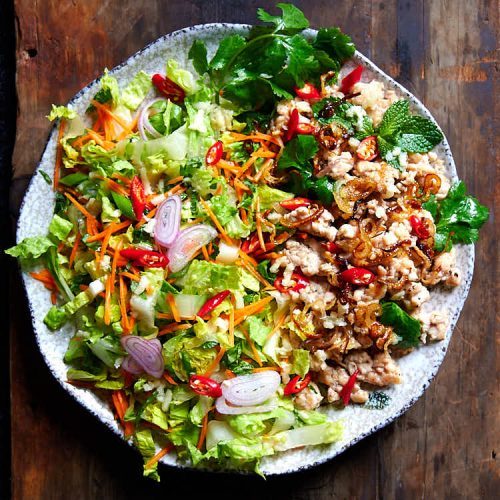 Thai larb gai - fried ground chicken, shredded cabbage, and fresh herbs on a round plate.