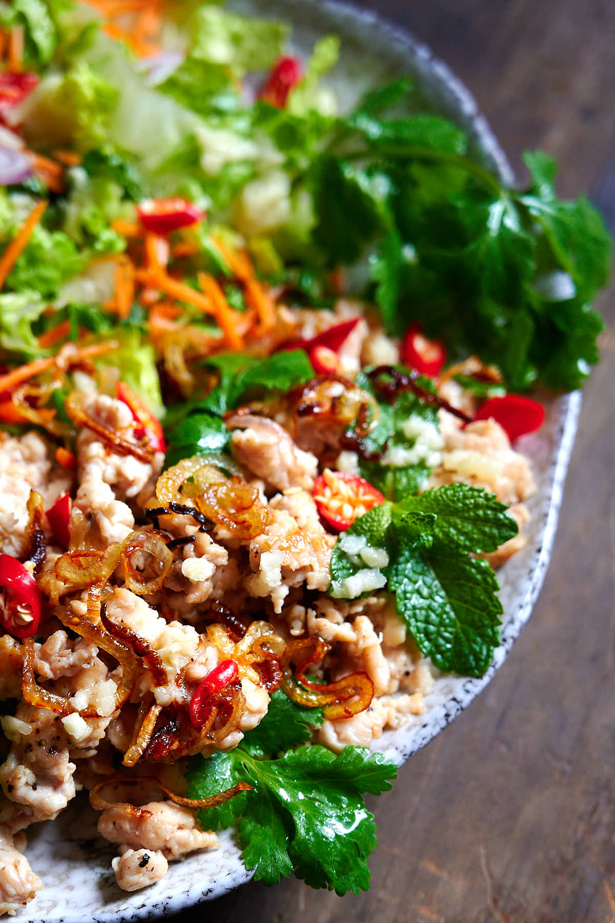 To view of larb gai - plate filled with shredded chicken, cabbage leaves, mint, basil and coriander leaves, sliced scallions and Thai red peppers, and seasoned with Thai dressing.