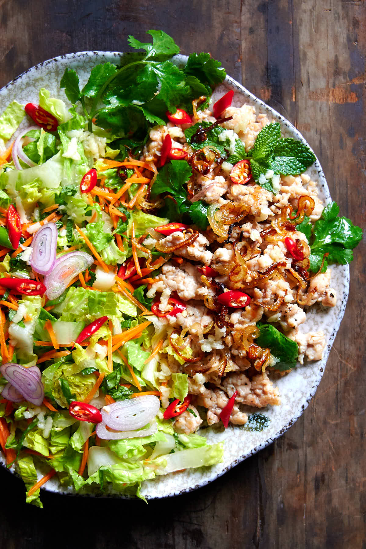 Thai chicken larb on a grey speckled plate - chicken, fresh herbs and chile peppers.
