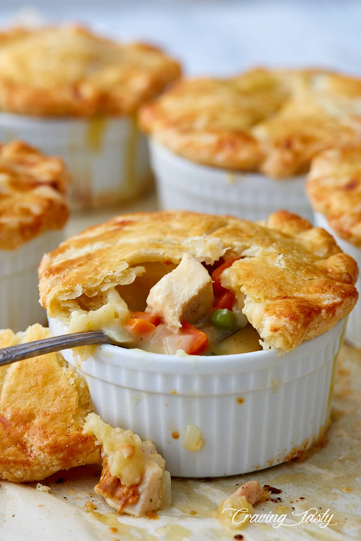 Several chicken pot pies on a baking dish, with the pie on the forefront split open and a spoon inserted into filling.