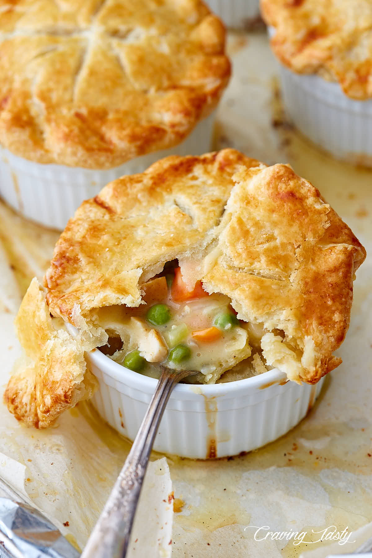 Chicken pot pie, in a ramekin, part of crust removed, a spoon inserted into creamy pie filling, chunks of chicken, peas and carrots visible.
