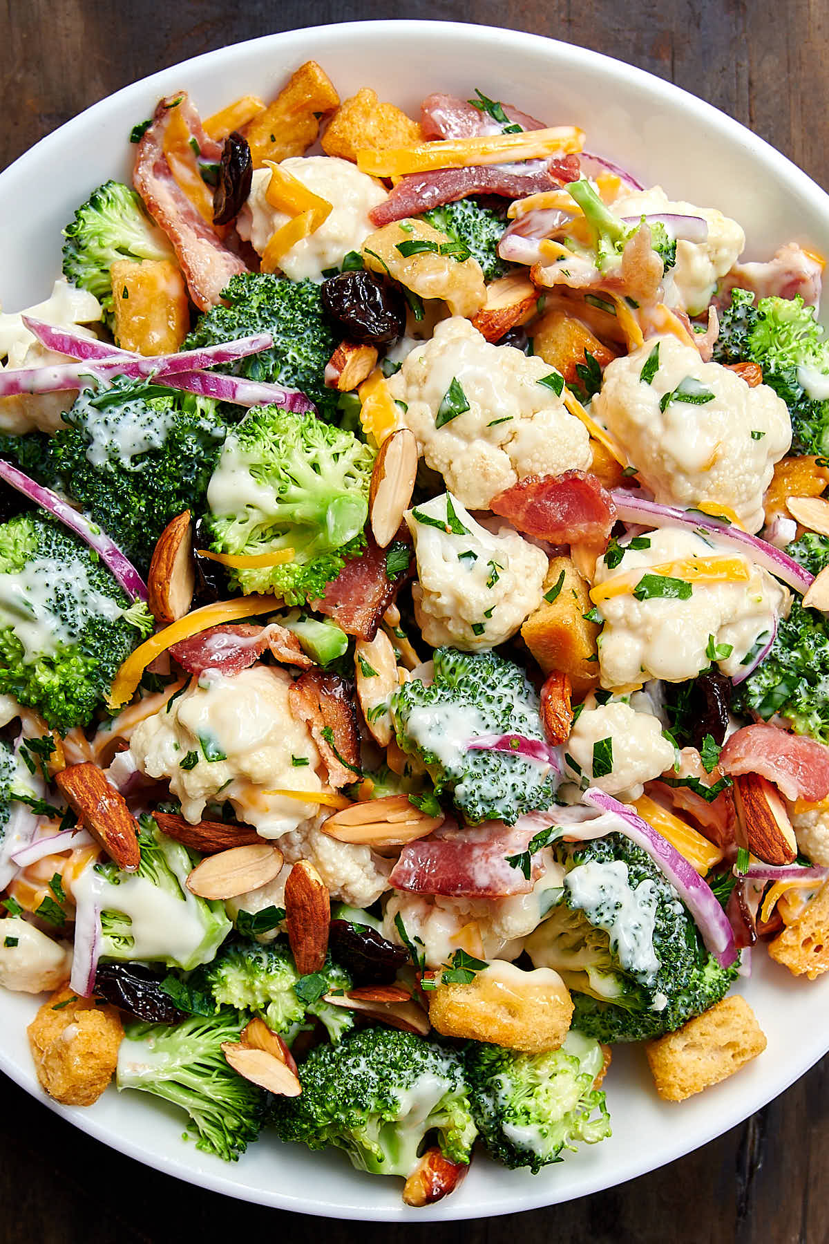 Broccoli and cauliflower salad (recipe) tossed with creamy dressing in white bowl.