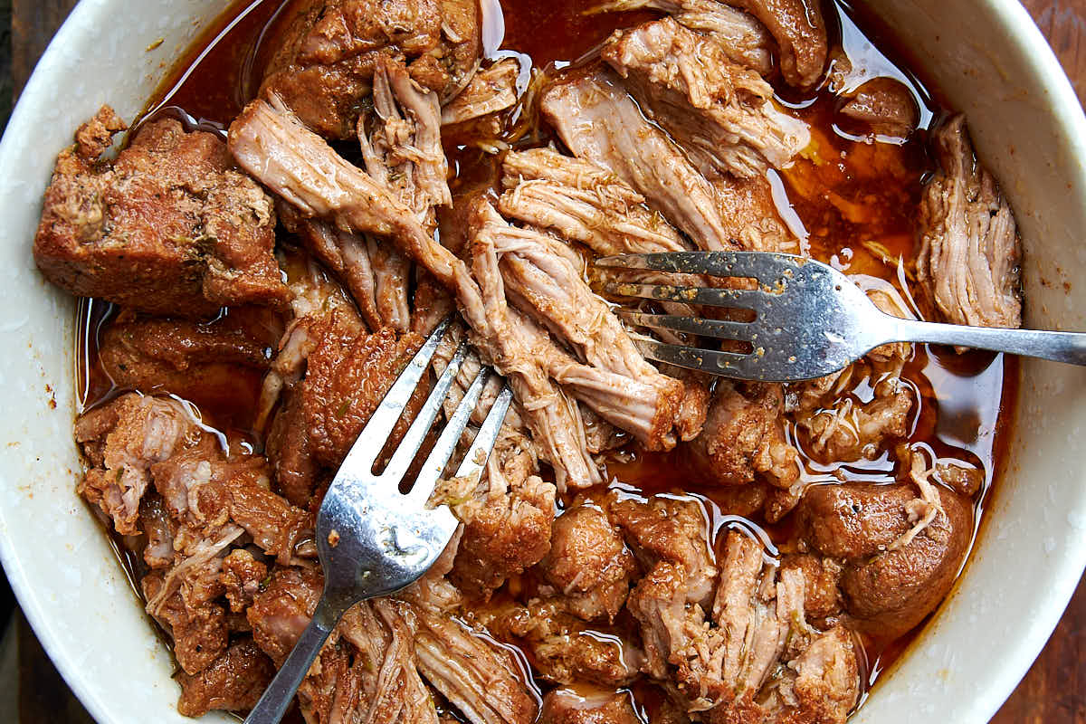 Pulled pork, cooked in pressure cooker, in a bowl with juices.