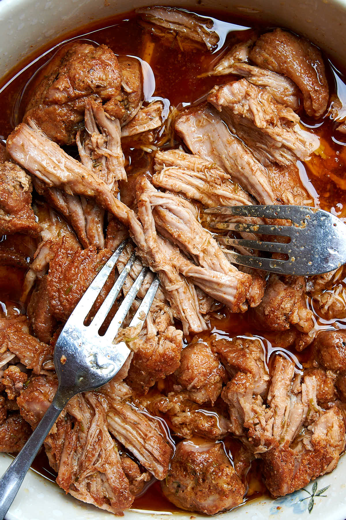Pork being pulled apart in a bowl with amber juices.
