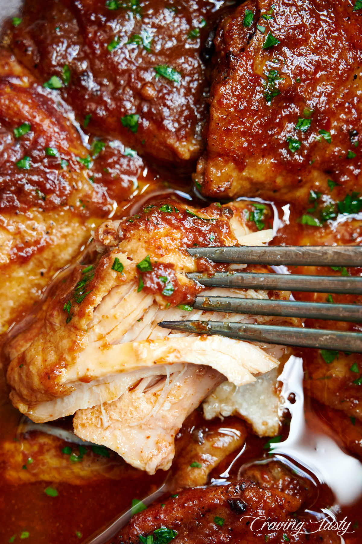 Close up of BBQ chicken inside slow cooker shredded with a fork.