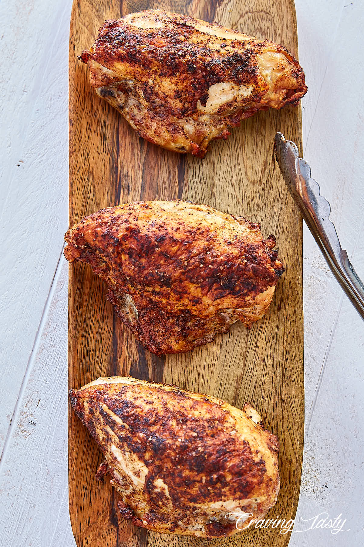 Top down view of three crispy-skinned, tender and juicy oven roasted bone-in chicken breasts on a wooden serving platter.