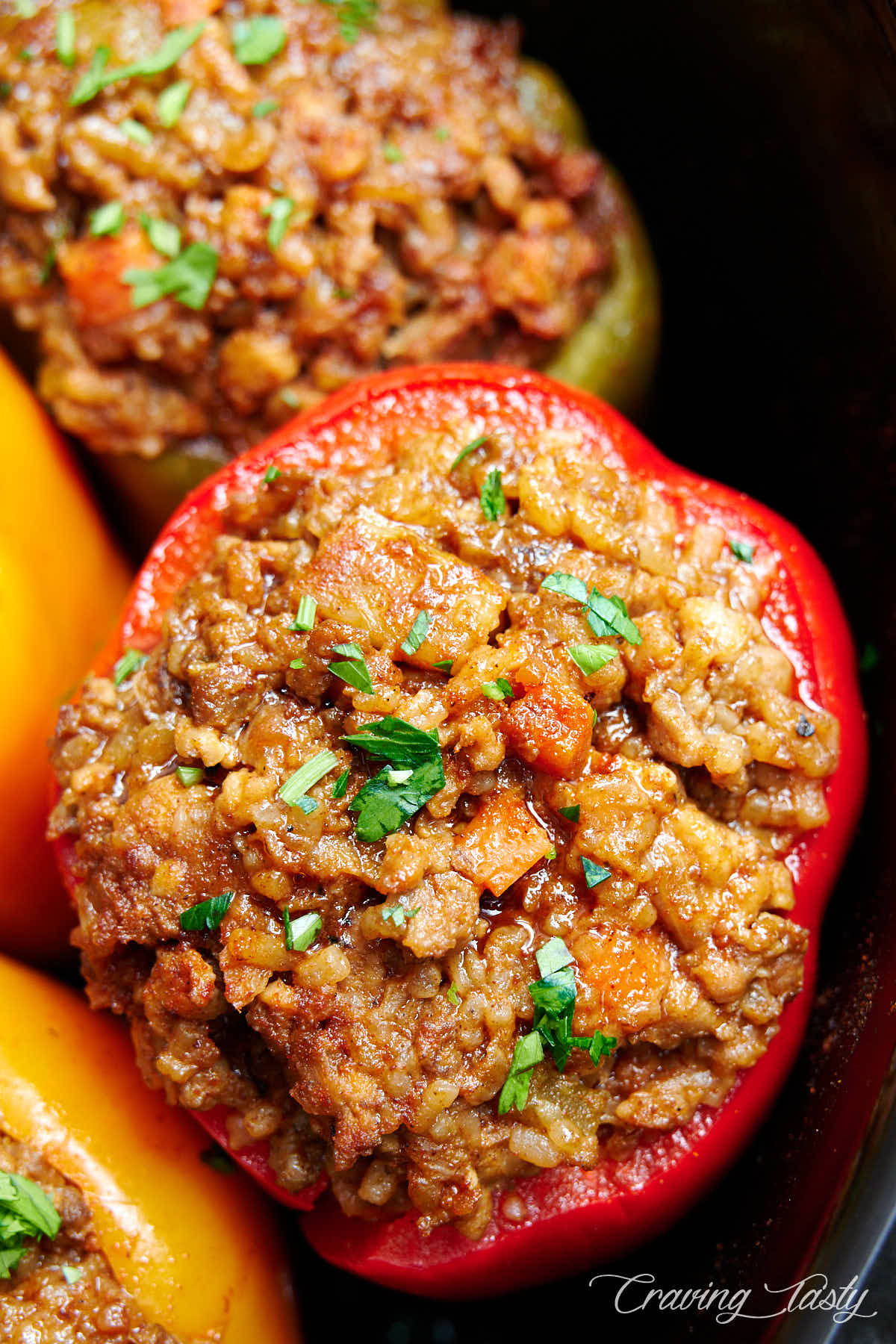 Red bell pepper stuffed with minced meat and garnished with chopped parsley.