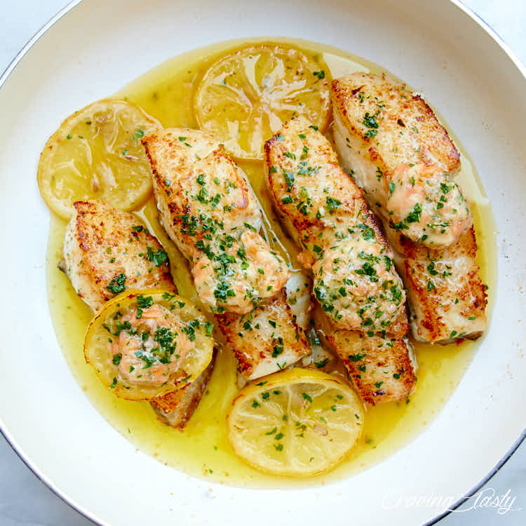 Seared halibut filets in oil in a white pan, with lemon slices .