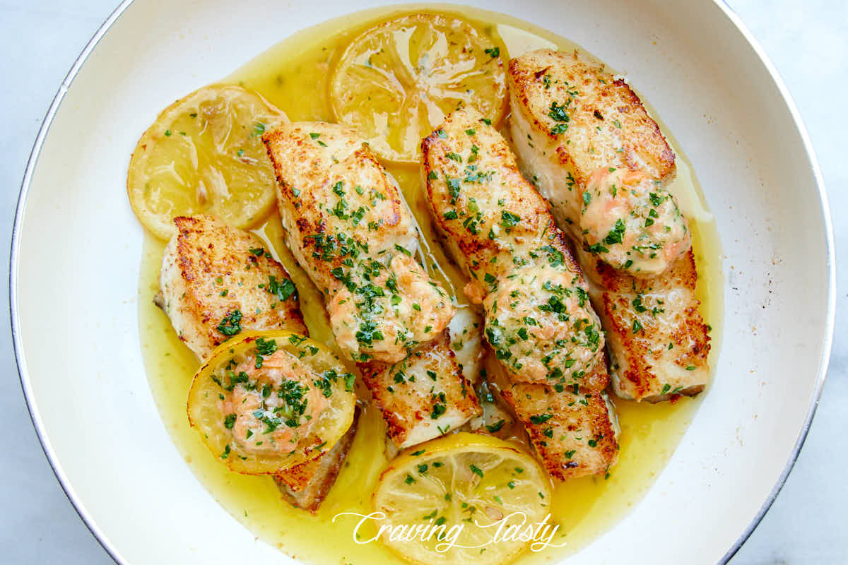 Four well browned halibut steaks in a white pan with oil, lemon slices and salmon butter on top.