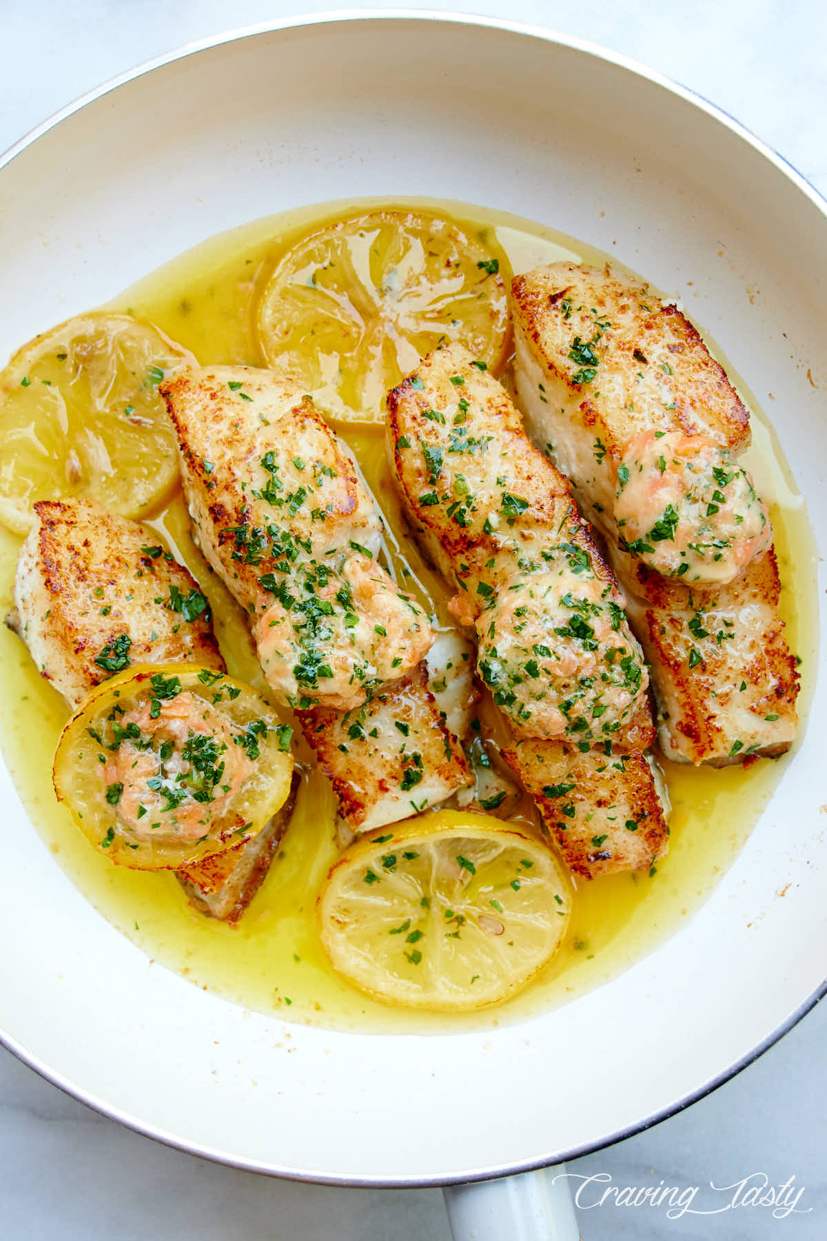Seared halibut pieces in oil in a white pan, with lemon slices .